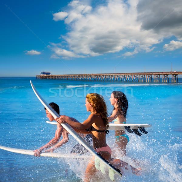 Teenager surfers running jumping on surfboards Stock photo © lunamarina