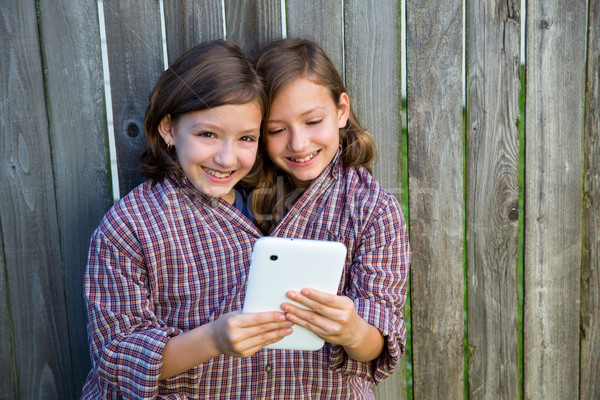 twin girls dressed up pretending be siamese and tablet pc Stock photo © lunamarina