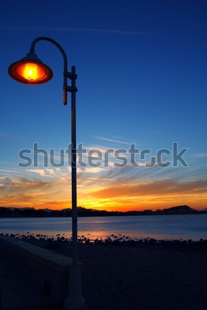 Sunset orange blue seascape light lamppost Stock photo © lunamarina