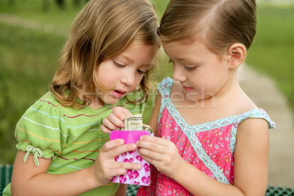 Two little twin girls find a dollar note inside a box Stock photo © lunamarina