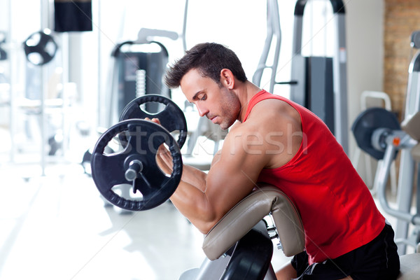 man with weight training equipment on sport gym Stock photo © lunamarina