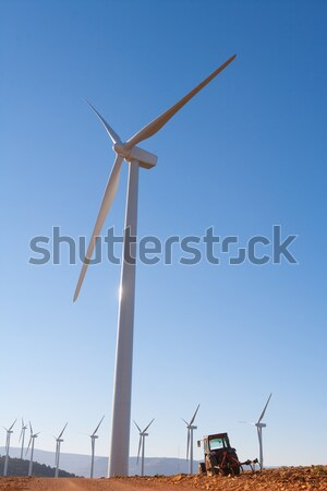 Agriculture tractor under electric wind mills in blue sky Stock photo © lunamarina