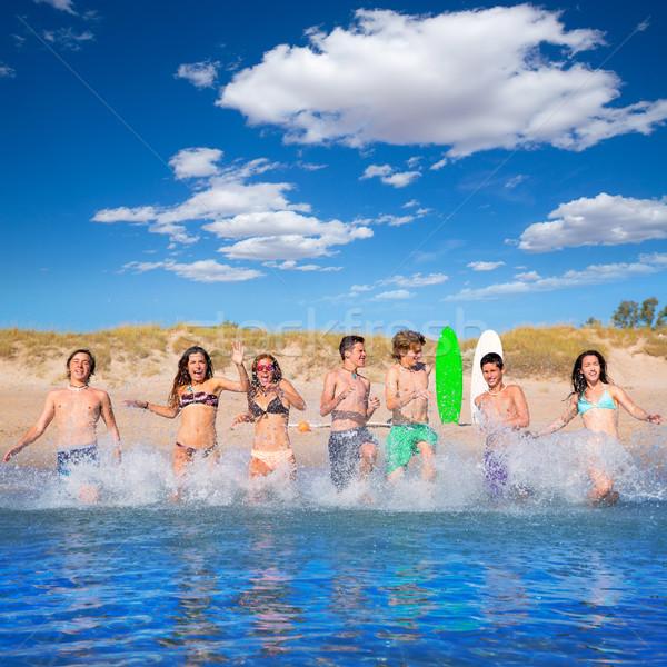 Teen surfers group running beach splashing Stock photo © lunamarina