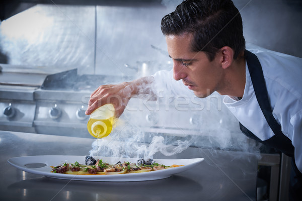 Chef preparing octopus in kitchen with smoke Stock photo © lunamarina