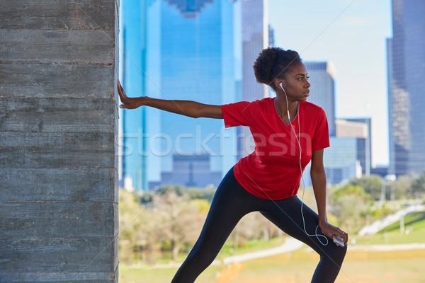 Runner girl stretching listening music earphones Stock photo © lunamarina