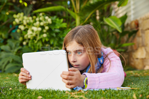Blond kid girl with tablet pc lying on grass turf Stock photo © lunamarina