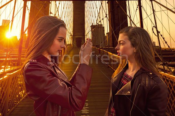 Teen tourist girls taking photo in Brooklyn bridge NY Stock photo © lunamarina