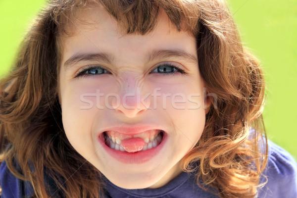 indented girl sticking tongue between teeth Stock photo © lunamarina