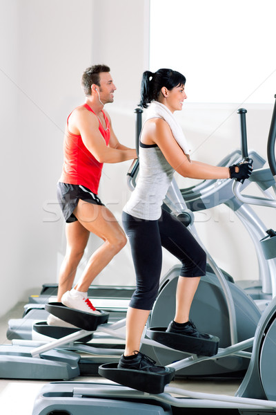 man and woman with elliptical cross trainer at gym Stock photo © lunamarina