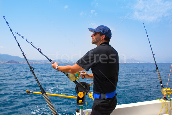 blue sea fisherman in trolling boat with downrigger Stock photo © lunamarina