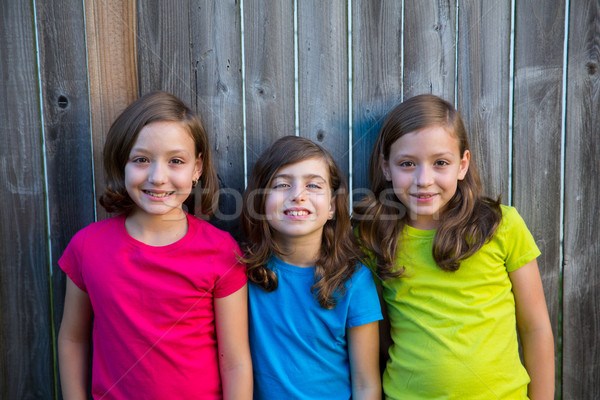 Sister and friends kid girls portrait smiling on gray fence Stock photo © lunamarina