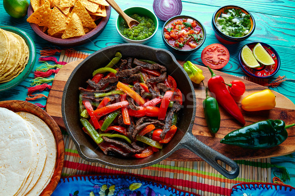 Beef fajitas in a pan sauces chili and sides Mexican Stock photo © lunamarina