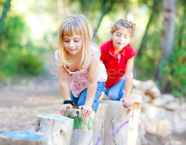 kid girls playing on trunks in forest nature Stock photo © lunamarina