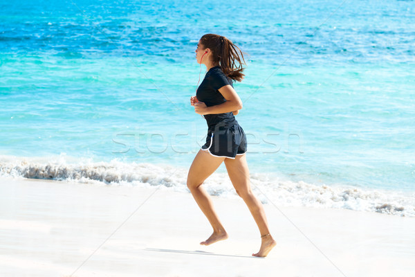 Latin girl running in caribbean shore beach Stock photo © lunamarina