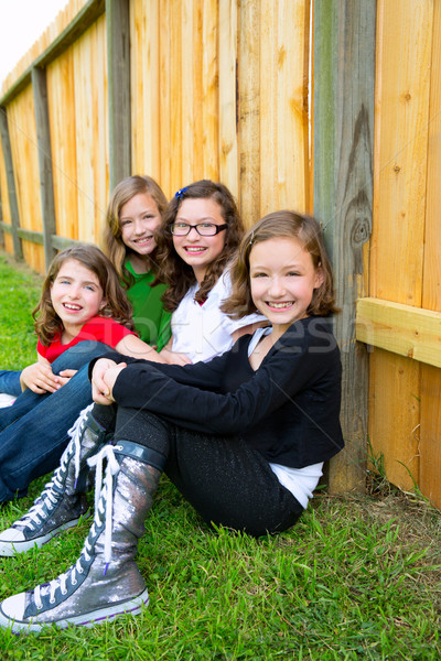 Grils group in a row smiling in a wooden fence Stock photo © lunamarina