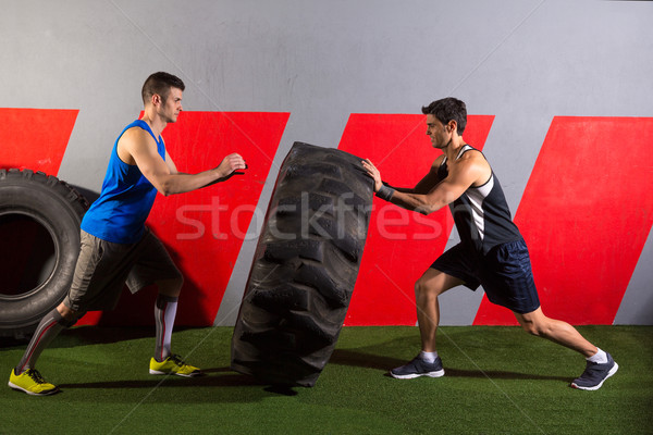 men flipping a tractor tire workout gym exercise Stock photo © lunamarina