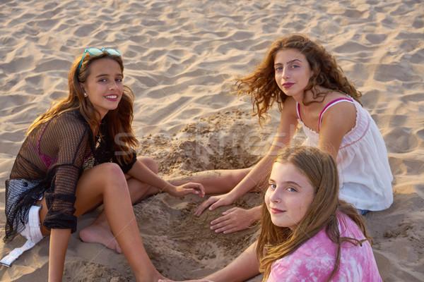 Three teen girls playing with the beach sand Stock photo © lunamarina