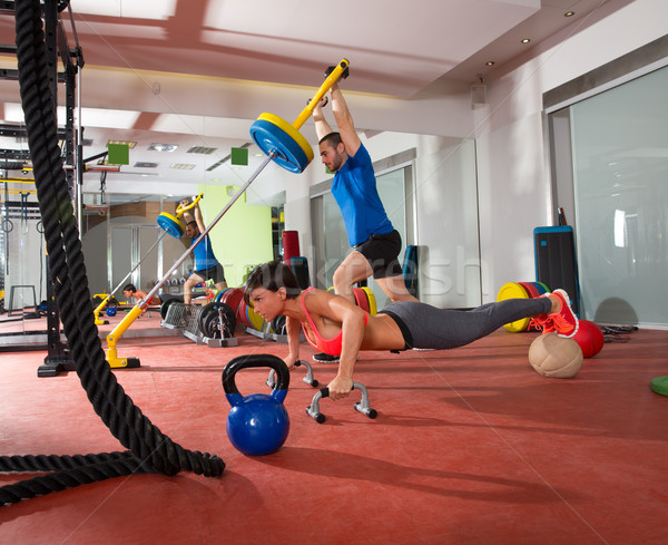 Crossfit woman push ups exercise and man weight lifting Stock photo © lunamarina
