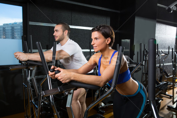 elliptical walker trainer man and woman at black gym Stock photo © lunamarina
