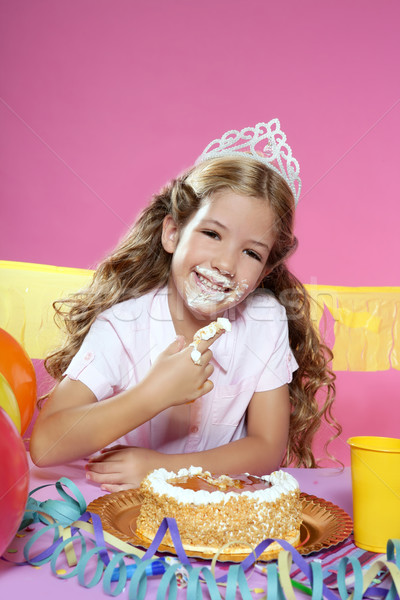 Stock photo: little blond birthday party girleating cake with hands