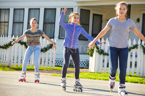 Teen girls group rolling skate in the street Stock photo © lunamarina