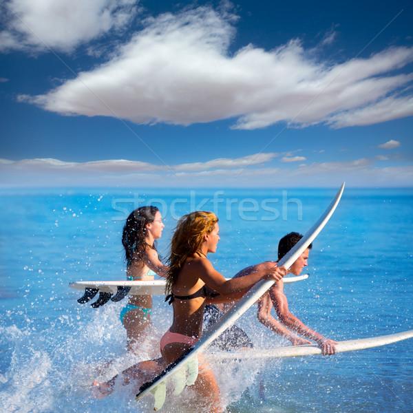 Boys and girls teen surfers running jumping on surfboards Stock photo © lunamarina