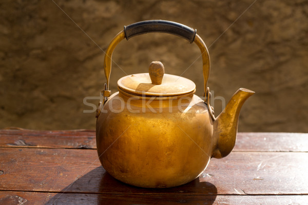 Antique brass teapot on vintage wood table Stock photo © lunamarina