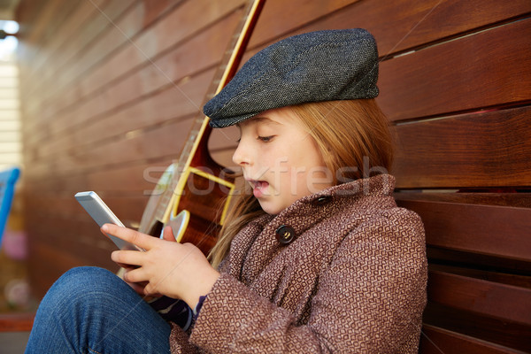 blond kid girl playing smartphone winter beret Stock photo © lunamarina
