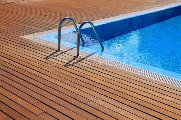 blue swimming pool with teak wood flooring Stock photo © lunamarina