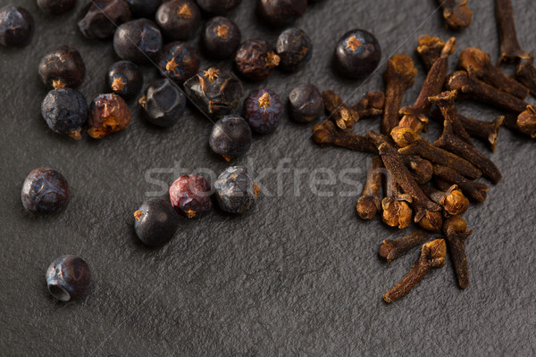 cloves and juniper berries spices on black slate stone Stock photo © lunamarina