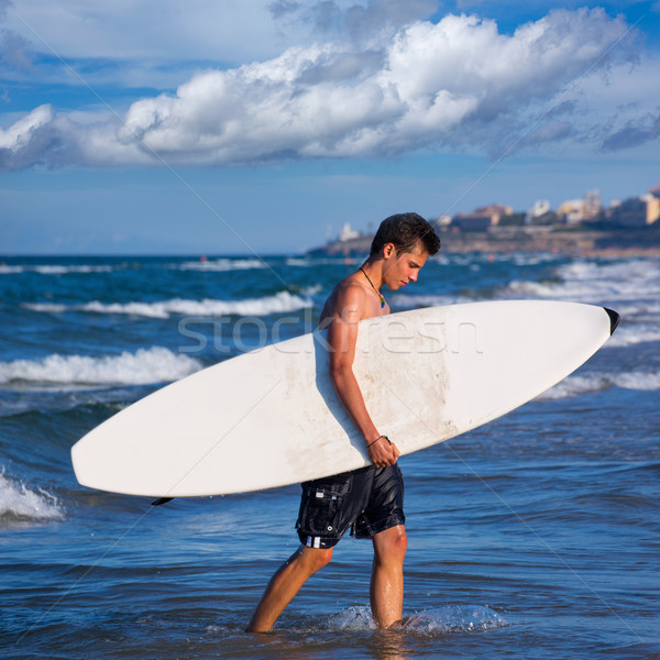 boy surfer holding surfboard caming out from the waves Stock photo © lunamarina