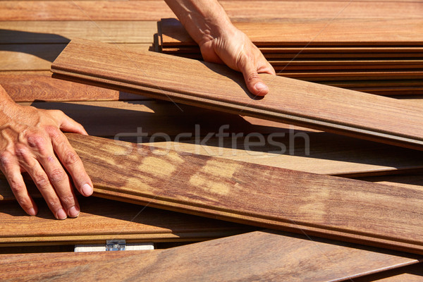 Ipe deck installation carpenter hands holding wood Stock photo © lunamarina