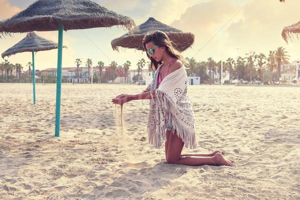Teen girl on the beach playing with sand Stock photo © lunamarina