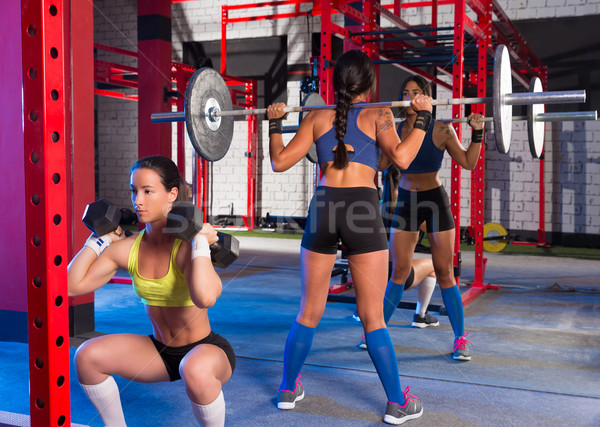Gym women with barbell and hex dumbbell Stock photo © lunamarina