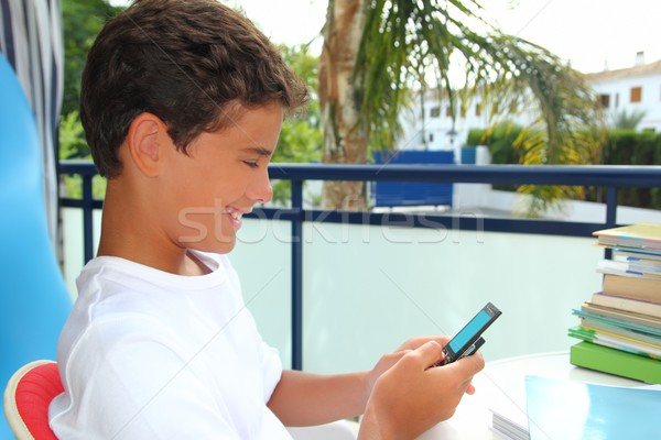 Teenager student boy sms message on moblile Stock photo © lunamarina