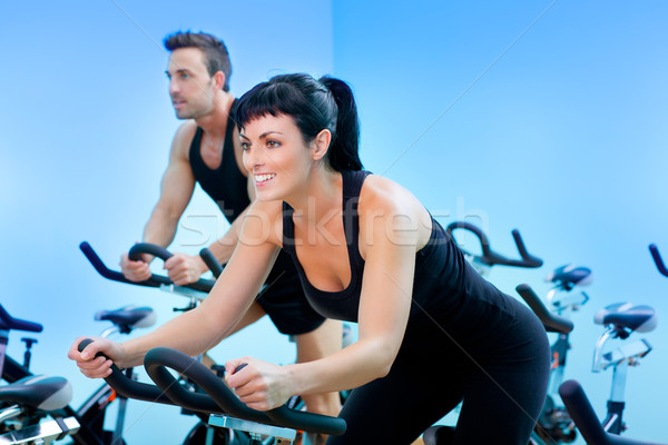 Stationary spinning bicycles fitness girl in a gym Stock photo © lunamarina