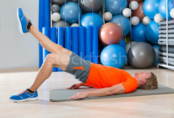 hip lift with leg extension blond man gym exercise Stock photo © lunamarina