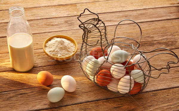 Eggs flour and milk in a vintage hen shape basket on wood Stock photo © lunamarina