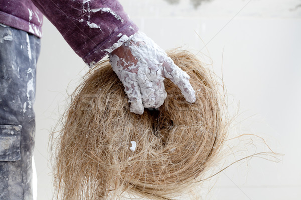 Plaster dirty hand with hemp for plasterboard Stock photo © lunamarina