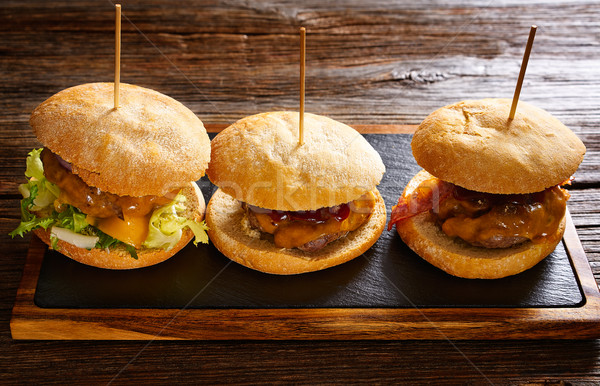 Burgers in a row on a slate board Stock photo © lunamarina