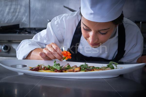 Chef woman garnishing flower in dish at kitchen Stock photo © lunamarina