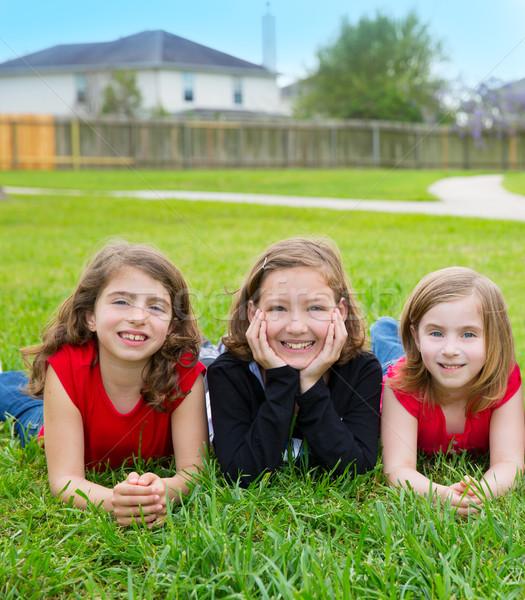 Children girls group lying on lawn grass smiling happy Stock photo © lunamarina