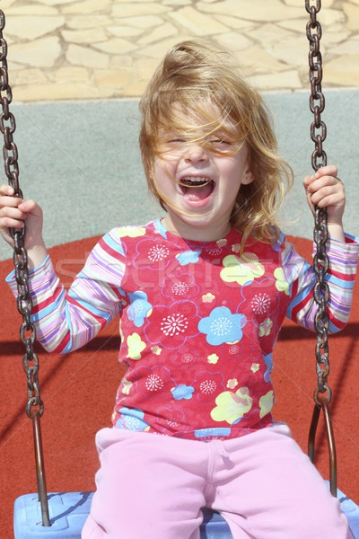 blond little girl swinging in park swing messy hair Stock photo © lunamarina