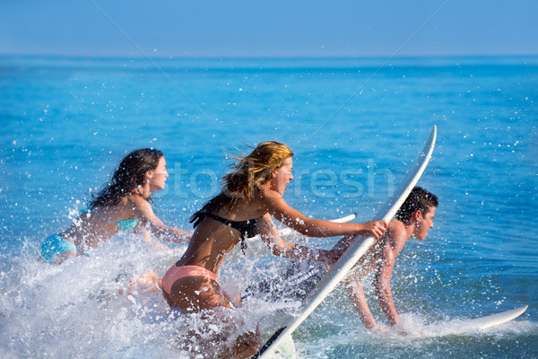 Boys and girls teen surfers surfing on surfboards Stock photo © lunamarina