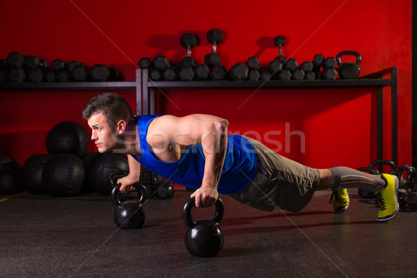 Kettlebells push-up man strength gym workout Stock photo © lunamarina