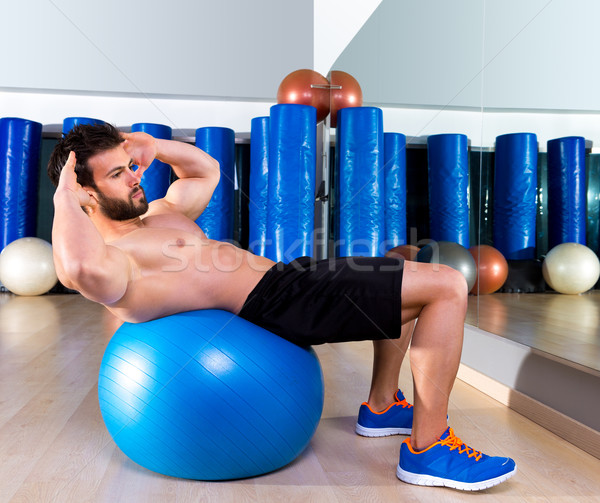 Fitball abdominal crunch Swiss ball man at gym Stock photo © lunamarina