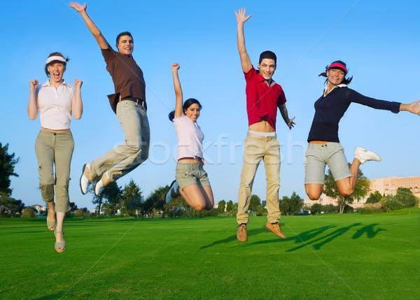 Foto stock: Grupo · jovens · saltando · ao · ar · livre · grama · feliz