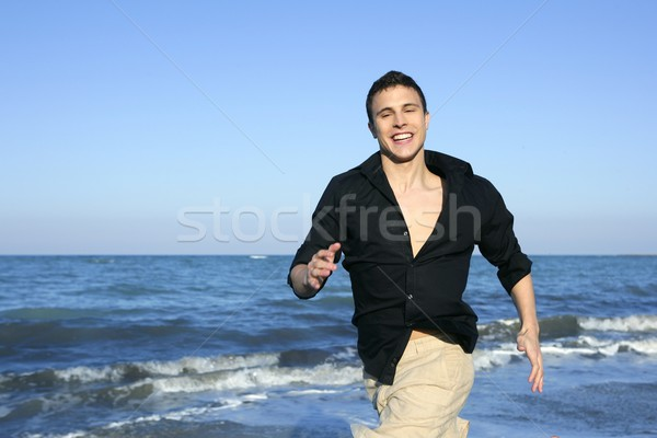 Man running happy on the blue summer beach Stock photo © lunamarina