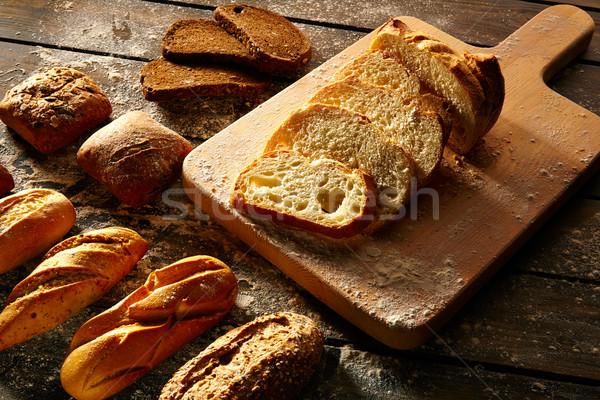 Stock photo: Bread varied loafs sliced on wood board in rustic