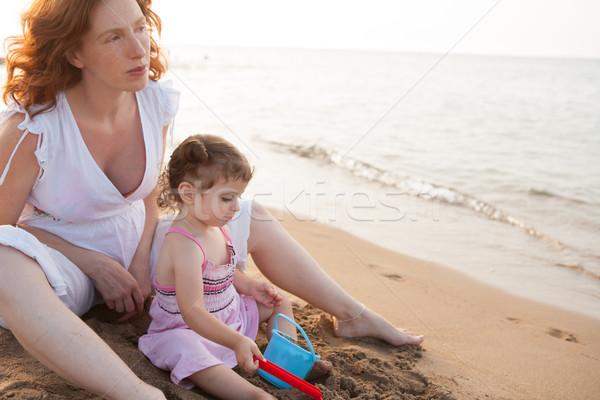 Terhes anya lánygyermek játszik tengerparti homok mediterrán Stock fotó © lunamarina